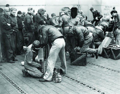 Crew members loading 50-caliber ammunition into trays prior to their launch from the USS Hornet as members of the US Navy watch. (Courtesy:  US Air Force Archives)